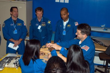 KENNEDY SPACE CENTER, FLA. - Members of the STS-116 crew examine components of the mission payload at SPACEHAB in Cape Canaveral, Fla. From left are Pilot William Ofelein and Mission Specialists Christer Fuglesang, Robert Curbeam and Nicholas Patrick. In the foreground at left is Mission Specialist Joan Higginbotham. The Swedish Fuglesang represents the European Space Agency. They are practicing opening a stowage bag. Mission crews make frequent trips to the Space Coast to become familiar with the equipment and payloads they will be using. STS-116 will be mission number 20 to the International Space Station and construction flight 12A.1. The mission payload is the SPACEHAB module, the P5 integrated truss structure and other key components. Launch is scheduled for no earlier than Dec. 7. Photo credit: NASA/George Shelton