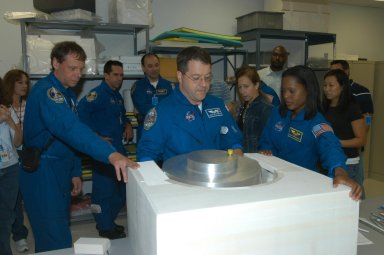 KENNEDY SPACE CENTER, FLA. - At SPACEHAB in Cape Canaveral, Fla., STS-116 crew members get a close look at he Treadmill Vibration Isolation System Gyroscop during equipment familiarization. Mission Specialist Nicholas Patrick (center) practices stowing the replacement gyro in the block of foam which is what the gyro will be stowed in inside the SPACEHAB module. The other crew members watching are, from left, Mission Specialists Christer Fuglesang, Pilot William Oefelein, Commander Mark Polansky, and at right, Mission Specialist Joan Higginbotham. Fuglesang, from Sweden, represents the European Space Agency. Between Patarick and Higginbotham is astronaut Marsha Ivins, who is currently assigned to the Astronaut Office, Space Station/Shuttle Branches for crew equipment, habitability and stowage. Mission crews make frequent trips to the Space Coast to become familiar with the equipment and payloads they will be using. STS-116 will be mission number 20 to the International Space Station and construction flight 12A.1. The mission payload is the SPACEHAB module, the P5 integrated truss structure and other key components. Launch is scheduled for no earlier than Dec. 7. Photo credit: NASA/George Shelton