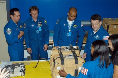 KENNEDY SPACE CENTER, FLA. - Members of the STS-116 crew examine components of the mission payload at SPACEHAB in Cape Canaveral, Fla. Looking at a stowage bag are, clockwise from left, Pilot William Ofelein and Mission Specialists Christer Fuglesang, Robert Curbeam, Nicholas Patrick and Joan Higginbotham. The Swedish Fuglesang represents the European Space Agency. Mission crews make frequent trips to the Space Coast to become familiar with the equipment and payloads they will be using. STS-116 will be mission number 20 to the International Space Station and construction flight 12A.1. The mission payload is the SPACEHAB module, the P5 integrated truss structure and other key components. Launch is scheduled for no earlier than Dec. 7. Photo credit: NASA/George Shelton