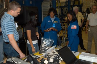 KENNEDY SPACE CENTER, FLA. - At SPACEHAB in Cape Canaveral, Fla., STS-116 Mission Specialists Sunita Williams (left) and Joan Higginbotham get a close look at the rack front stowage trays that are used inside the SPACEHAB module. Mission crews make frequent trips to the Space Coast to become familiar with the equipment and payloads they will be using. STS-116 will be mission number 20 to the International Space Station and construction flight 12A.1. The mission payload is the SPACEHAB module, the P5 integrated truss structure and other key components. Launch is scheduled for no earlier than Dec. 7. Photo credit: NASA/George Shelton