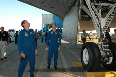 KENNEDY SPACE CENTER, FLA. - At the traditional post-landing inspection, STS-115 Mission Specialists Steven MacLean and Daniel Burbank examine the underside of the orbiter Atlantis. During the mission, astronauts completed three spacewalks to attach the P3/P4 integrated truss structure to the International Space Station. Main gear touchdown was at 6:21:30 a.m. EDT. Nose gear touchdown was at 6:21:36 a.m. and wheel stop was at 6:22:16 a.m. Atlantis traveled 4.9 million miles, landing on orbit 187. Mission elapsed time was 11 days, 19 hours, six minutes. This is the 15th night landing at KSC and the 23rd night landing overall. Photo credit: NASA/Kim Shiflett