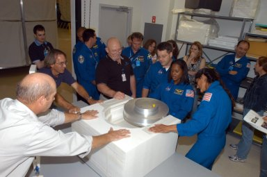 KENNEDY SPACE CENTER, FLA. - At SPACEHAB in Cape Canaveral, Fla., STS-116 crew members get a close look at the Treadmill Vibration Isolation System Gyroscope during equipment familiarization. The block of foam is what the replacement gyro will be stowed in inside the SPACEHAB module. In uniform from left are Pilot William Oefelein and Mission Specialists Christer Fuglesang, Nicholas Patrick, Joan Higginbotham and Sunita Williams. In the background at right is Commander Mark Polansky. Fuglesang, from Sweden, represents the European Space Agency. Mission crews make frequent trips to the Space Coast to become familiar with the equipment and payloads they will be using. STS-116 will be mission number 20 to the International Space Station and construction flight 12A.1. The mission payload is the SPACEHAB module, the P5 integrated truss structure and other key components. Launch is scheduled for no earlier than Dec. 7. Photo credit: NASA/George Shelton