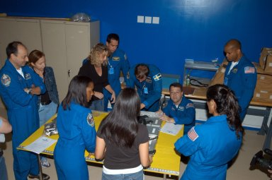 KENNEDY SPACE CENTER, FLA. - Members of the STS-116 crew examine components of the mission payload at SPACEHAB in Cape Canaveral, Fla. From left (in their blue uniforms) around the table are Commander Mark Polansky and Mission Specialists Joan Higginbotham, Christer Fuglesang, Nicholas Patrick, Sunita Williams and Robert Curbeam. In the background is Pilot William Oefelein. The Swedish Fuglesang represents the European Space Agency. They are practicing techniques for removing and replacing the rack front stowage trays used inside the SPACEHAB module. Mission crews make frequent trips to the Space Coast to become familiar with the equipment and payloads they will be using. STS-116 will be mission number 20 to the International Space Station and construction flight 12A.1. The mission payload is the SPACEHAB module, the P5 integrated truss structure and other key components. Launch is scheduled for no earlier than Dec. 7. Photo credit: NASA/George Shelton