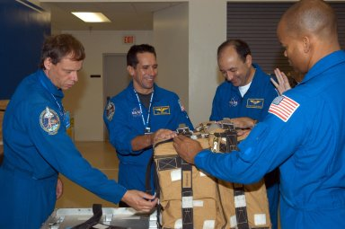 KENNEDY SPACE CENTER, FLA. - Members of the STS-116 crew examine components of the mission payload at SPACEHAB in Cape Canaveral, Fla. From left are Mission Specialist Christer Fuglesang , Pilot William Oefelein, Commander Mark Polansky and Mission Specialist Robert Curbeam, who practice opening and closing a stowage bag. Fuglesang, from Sweden, represents the European Space Agency. Mission crews make frequent trips to the Space Coast to become familiar with the equipment and payloads they will be using. STS-116 will be mission number 20 to the International Space Station and construction flight 12A.1. The mission payload is the SPACEHAB module, the P5 integrated truss structure and other key components. Launch is scheduled for no earlier than Dec. 7. Photo credit: NASA/George Shelton