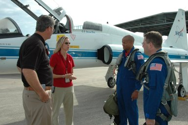 KENNEDY SPACE CENTER, FLA. - From left, at Kennedy Space Center?s Shuttle Landing Facility, Deputy Director William Parsons and Discovery Flow Director Stephanie Stilson greet STS-116 Mission Specialists Robert Curbeam and Nicholas Patrick after they arrive for the Crew Equipment Interface Test. Mission crews make frequent trips to the Space Coast to become familiar with the equipment and payloads they will be using. STS-116 will be mission No. 20 to the International Space Station and construction flight 12A.1. The mission payload is the SPACEHAB module, the P5 integrated truss structure and other key components. Launch is scheduled for no earlier than Dec. 7. Photo credit: NASA/Kim Shiflett