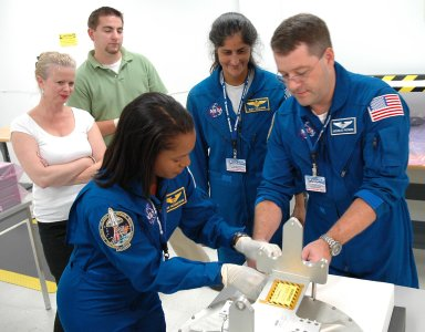 KENNEDY SPACE CENTER, FLA. - Inside the SPACEHAB Payload Processing Facility at Port Canaveral, Fla., STS-116 Mission Specialists (from left) Joan Higginbotham, Sunita Williams and Nicholas Patrick look over flight hardware during the Crew Equipment Interface Test. Mission crews make frequent trips to the Space Coast to become familiar with the equipment and payloads they will be using. STS-116 will be mission No. 20 to the International Space Station and construction flight 12A.1. The mission payload is the SPACEHAB module, the P5 integrated truss structure and other key components. Launch is scheduled for no earlier than Dec. 7. Photo credit: NASA/Kim Shiflett