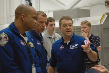 KENNEDY SPACE CENTER, FLA. - In the Orbiter Processing Facility, members of the STS-116 crew discuss use of some of the flight hardware during the Crew Equipment Interface Test. Seen here are (from left) Mission Specialists Robert Curbeam, Christer Fugelsang and Nicholas Patrick. Fugelsang represents the European Space Agency. Mission crews make frequent trips to the Kennedy Space Center to become familiar with the equipment and payloads they will be using. STS-116 will be mission No. 20 to the International Space Station and construction flight 12A.1. The mission payload is the SPACEHAB module, the P5 integrated truss structure and other key components. Launch is scheduled for no earlier than Dec. 7. Photo credit: NASA/Kim Shiflett