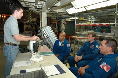 KENNEDY SPACE CENTER, FLA. - STS-116 crew members (at right) are briefed on the cameras they will be using during the mission. The astronauts are, from left, Mission Specialists Robert Curbeam and Christer Fugelsang and Pilot William Oefelein. The crew is at KSC for a Crew Equipment Interface Test. Mission crews make frequent trips to the Kennedy Space Center to become familiar with the equipment and payloads they will be using. STS-116 will be mission No. 20 to the International Space Station and construction flight 12A.1. The mission payload is the SPACEHAB module, the P5 integrated truss structure and other key components. Launch is scheduled for no earlier than Dec. 7. Photo credit: NASA/Kim Shiflett