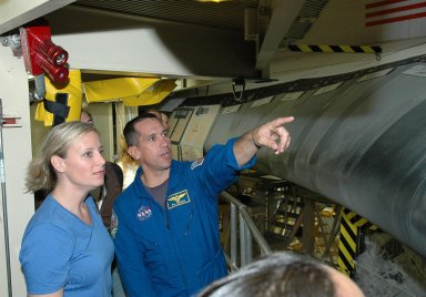 KENNEDY SPACE CENTER, FLA. - From a platform in the Orbiter Processing Facility, STS-116 Pilot William Oefelein points to Discovery?s reinforced carbon-carbon wing leading edge. He and other crew members are at KSC for a Crew Equipment Interface Test. Mission crews make frequent trips to the Kennedy Space Center to become familiar with the equipment and payloads they will be using. STS-116 will be mission No. 20 to the International Space Station and construction flight 12A.1. The mission payload is the SPACEHAB module, the P5 integrated truss structure and other key components. Launch is scheduled for no earlier than Dec. 7. Photo credit: NASA/Kim Shiflett