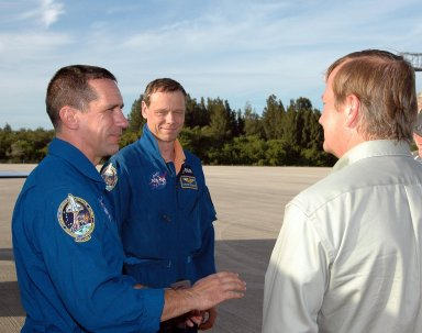 KENNEDY SPACE CENTER, FLA. -- STS-116 Pilot William Oefelein (left) and Mission Specialist Christer Fuglesang are greeted by Shuttle Launch Director Mike Leinbach (right) at the Shuttle Landing Facility. The STS-116 crew has returned to KSC for the terminal countdown demonstration test, which are pre-launch preparations that include a simulated launch countdown. The crew also includes Commander Mark Polansky, Mission Specialists Nicholas Patrick, Robert Curbeam, Joan Higginbotham and Flight Engineer Sunita Williams, joining Expedition 14 in progress. The mission is No. 20 to the International Space Station and construction flight 12A.1. The mission payload is the SPACEHAB module, the P5 integrated truss structure and other key components. Launch is scheduled for no earlier than Dec. 7. Photo credit: NASA/Kim Shiflett