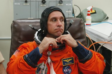 KENNEDY SPACE CENTER, FLA. -- The STS-116 mission crew practices for launch with a simulation of activities, from crew breakfast and suit-up to countdown in the orbiter. In this photo Pilot William Oefelein fixes the neck of his launch suit before heading to Launch Pad 39B. The STS-116 mission is No. 20 to the International Space Station and construction flight 12A.1. The mission payload is the SPACEHAB module, the P5 integrated truss structure and other key components. Launch is scheduled for no earlier than Dec. 7. Photo credit: NASA/Kim Shiflett