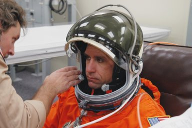 KENNEDY SPACE CENTER, FLA. -- The STS-116 mission crew practices for launch with a simulation of activities, from crew breakfast and suit-up to countdown in the orbiter. In this photo Pilot William Oefelein has his helmet adjusted before heading to Launch Pad 39B. The STS-116 mission is No. 20 to the International Space Station and construction flight 12A.1. The mission payload is the SPACEHAB module, the P5 integrated truss structure and other key components. Launch is scheduled for no earlier than Dec. 7. Photo credit: NASA/Kim Shiflett