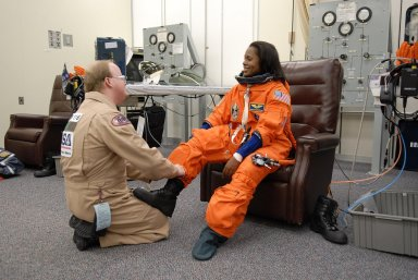 KENNEDY SPACE CENTER, FLA. -- The crew members of mission STS-116 are suiting up for launch at 9:35 p.m. EST from Launch Pad 39B aboard Space Shuttle Discovery. Pictured here, Mission Specialist Joan Higginbotham is helped with her boot. Higginbotham will be making her first shuttle flight. This is Discovery's 33rd mission and the first night launch since 2003. The 20th shuttle mission to the International Space Station, STS-116 carries another truss segment, P5. It will serve as a spacer, mated to the P4 truss that was attached in September. After installing the P5, the crew will reconfigure and redistribute the power generated by two pairs of U.S. solar arrays. Landing is expected Dec. 19 at KSC. Photo credit: NASA/Kim Shiflett