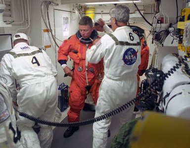 KENNEDY SPACE CENTER, FLA. - In the White Room on Launch Pad 39B, STS-121 Mission Specialist Michael Fossum gets help from the Closeout Crew with final preparations on his launch suit before entering Discovery. Situated on the end of the orbiter access arm, the White Room provides access into the orbiter on the pad. The crew is preparing for the third launch attempt in four days; previous attempts were scrubbed due to weather concerns. During the 12-day mission, the STS-121 crew will test new equipment and procedures to improve shuttle safety, as well as deliver supplies and make repairs to the International Space Station. The launch of Space Shuttle Discovery on mission STS-121 is the 115th shuttle flight and the 18th U.S. flight to the International Space Station.