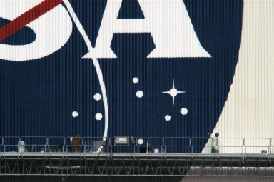 """KENNEDY SPACE CENTER, FLA. -- Elevated platforms are seen hanging on the side of Kennedy Space Center's Vehicle Assembly Building to facilitate the repainting of the American flag and NASA logo. Workers, suspended on the platforms from the top of the 525-foot-high VAB, use rollers and brushes to do the painting. The flag and logo were last painted in 1998, honoring NASA's 40th anniversary. The flag spans an area 209 feet by 110 feet, or about 23, 437 square feet. Each stripe is 9 feet wide and each star is 6 feet in diameter. The logo, also known as the """"meatball,"""" measures 110 feet by 132 feet, or about 12,300 square feet. Photo credit: NASA/George Shelton"""