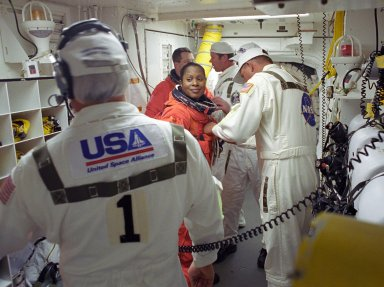 KENNEDY SPACE CENTER, FLA. -- STS-116 Mission Specialist Joan Higginbotham is helped by the closeout crew in the White Room to secure her launch suit before climbing into Space Shuttle Discovery. Behind her is Mission Specialist Nicholas Patrick. The White Room is at the end of the orbiter access arm that extends from the fixed service structure and provides entry into the orbiter. The first launch attempt of STS-116 on Dec. 7 was postponed due a low cloud ceiling over Kennedy Space Center. This second launch attempt is scheduled for 8:47 p.m. This is Discovery's 33rd mission and the first night launch since 2002. The 20th shuttle mission to the International Space Station, STS-116 carries another truss segment, P5. It will serve as a spacer, mated to the P4 truss that was attached in September. After installing the P5, the crew will reconfigure and redistribute the power generated by two pairs of U.S. solar arrays. Landing is expected Dec. 21 at KSC. Photo credit: NASA/Tony Gray & Don Kight