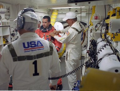 KENNEDY SPACE CENTER, FLA. -- STS-116 Commander William Oefelein is helped by the closeout crew in the White Room to secure his launch suit before climbing into Space Shuttle Discovery. The White Room is at the end of the orbiter access arm that extends from the fixed service structure and provides entry into the orbiter. The first launch attempt of STS-116 on Dec. 7 was postponed due a low cloud ceiling over Kennedy Space Center. This second launch attempt is scheduled for 8:47 p.m. This is Discovery's 33rd mission and the first night launch since 2002. The 20th shuttle mission to the International Space Station, STS-116 carries another truss segment, P5. It will serve as a spacer, mated to the P4 truss that was attached in September. After installing the P5, the crew will reconfigure and redistribute the power generated by two pairs of U.S. solar arrays. Landing is expected Dec. 21 at KSC. Photo credit: NASA/Tony Gray & Don Kight