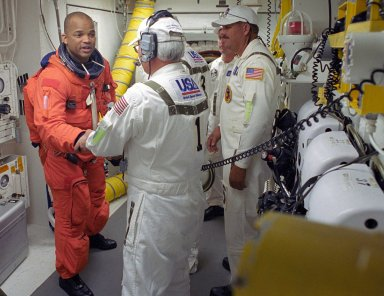 KENNEDY SPACE CENTER, FLA. -- STS-116 Mission Specialist Robert Curbeam thanks the closeout crew for their help in completing his suitup before climbing into Space Shuttle Discovery. The White Room is at the end of the orbiter access arm that extends from the fixed service structure and provides entry into the orbiter. The first launch attempt of STS-116 on Dec. 7 was postponed due a low cloud ceiling over Kennedy Space Center. This second launch attempt is scheduled for 8:47 p.m. This is Discovery's 33rd mission and the first night launch since 2002. The 20th shuttle mission to the International Space Station, STS-116 carries another truss segment, P5. It will serve as a spacer, mated to the P4 truss that was attached in September. After installing the P5, the crew will reconfigure and redistribute the power generated by two pairs of U.S. solar arrays. Landing is expected Dec. 21 at KSC. Photo credit: NASA/Tony Gray & Don Kight