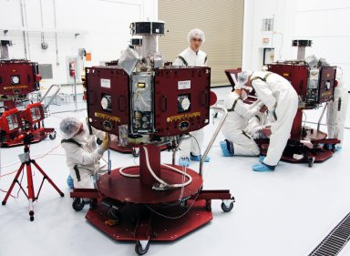 KENNEDY SPACE CENTER, FLA. -- In the Hazardous Processing Facility at Astrotech Space Operations, technicians prepare THEMIS probes for solar array illumination telemetry tests. THEMIS consists of five identical probes, the largest number of scientific satellites ever launched into orbit aboard a single rocket. This unique constellation of satellites will resolve the tantalizing mystery of what causes the spectacular sudden brightening of the aurora borealis and aurora australis - the fiery skies over the Earth's northern and southern polar regions. THEMIS is scheduled to launch aboard the Delta II at 6:07 p.m. EST on Feb. 15. Photo credit: NASA/George Shelton
