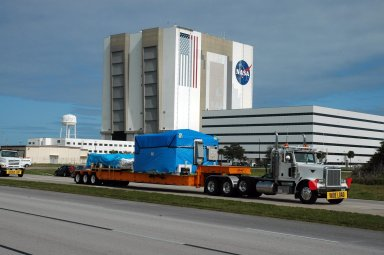 """KENNEDY SPACE CENTER, FLA. -- The truck transporting the remote manipulator system for the Japanese Experiment Module moves past the Vehicle Assembly Building on its way to the Space Station Processing Facility. The JEM, named """"Kibo"""" (Hope), is Japan's primary contribution to the International Space Station. It will enhance the unique research capabilities of the orbiting complex by providing an additional environment for astronauts to conduct science experiments. The Japanese Aerospace Exploration Agency developed the laboratory. Both the JEM and RMS are targeted for mission STS-124, to launch in early 2008. Photo credit: NASA/Dimitrios Gerondidakis"""