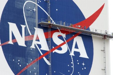 """KENNEDY SPACE CENTER, FLA. -- On platforms suspended from the top of the 525-foot-high VAB, workers use rollers and brushes to repaint the U.S. flag on the southwest side of the Vehicle Assembly Building. The flag spans an area 209 feet by 110 feet, or about 23, 437 square feet. Each stripe is 9 feet wide and each star is 6 feet in diameter. The logo is also being painted. Known as the """"meatball,"""" the logo measures 110 feet by 132 feet, or about 12,300 square feet. The flag and logo were last painted in 1998, honoring NASA's 40th anniversary. Photo credit: NASA/George Shelton"""
