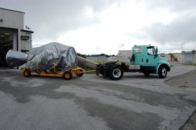 KENNEDY SPACE CENTER, FLA. -- The covered Delta II second stage arrives at a checkout hangar on Cape Canaveral Air Force Station in Florida in preparation for transfer to Pad 17-B. At the pad, it will be lifted into the mobile service tower and mated with the first stage already in place. The Delta II is the launch vehicle for the THEMIS spacecraft. THEMIS consists of five identical probes, the largest number of scientific satellites ever launched into orbit aboard a single rocket. This unique constellation of satellites will resolve the tantalizing mystery of what causes the spectacular sudden brightening of the aurora borealis and aurora australis - the fiery skies over the Earth's northern and southern polar regions. THEMIS is scheduled to launch Feb. 15 from Cape Canaveral Air Force Station. Photo credit: NASA/George Shelton