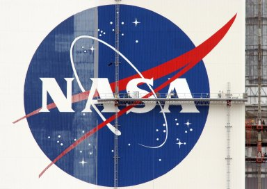 """KENNEDY SPACE CENTER, FLA. -- On platforms suspended from the top of the 525-foot-high VAB, workers use rollers and brushes to repaint the NASA logo on the southeast side of the Vehicle Assembly Building. Known as the """"meatball,"""" the logo measures 110 feet by 132 feet, or about 12,300 square feet. The U.S. flag is also being repainted. The flag spans an area 209 feet by 110 feet, or about 23, 437 square feet. Each stripe is 9 feet wide and each star is 6 feet in diameter. The flag and logo were last painted in 1998, honoring NASA's 40th anniversary. Photo credit: NASA/George Shelton"""