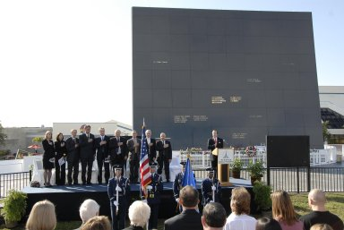"""KENNEDY SPACE CENTER, FLA. -- Guests and attendees salute the U.S. flag during a ceremony at the KSC Visitor Complex held in remembrance of the astronauts lost in the Apollo 1 fire: Virgil """"Gus"""" Grissom, Edward H. White II and Roger B. Chaffee. Among those gathered on stage are (from left) Faith Johnson, daughter of Theodore Freeman and Martha Chaffee, daughter of Roger Chaffee, Associate Administrator for Space Operations William Gerstenmaier and KSC Director Bill Parsons, plus former astronaut John Young and Lowell Grissom, brother of Gus Grissom (far right). At the podium is Stephen Feldman, president of the Astronauts Memorial Foundation. Behind the stage is the Space Mirror Memorial, designated as a national memorial by Congress and President George Bush in 1991 to honor fallen astronauts. Their names are emblazoned on the monument?s 42-½-foot-high by 50-foot-wide black granite surface as if to be projected into the heavens. Photo credit:NASA/Kim Shiflett"""