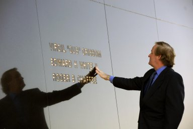 """KENNEDY SPACE CENTER, FLA. -- Ed White III touches his father's name engraved in the Space Mirror Memorial at the KSC Visitor Complex. White attended the ceremony held in remembrance of the astronauts lost in the Apollo 1 fire: Virgil """"Gus"""" Grissom, Edward H. White II and Roger B. Chaffee. Members of their families, along with KSC Director Bill Parsons, Associate Administrator for Space Operations William Gerstenmaier, President of the Astronauts Memorial Foundation Stephen Feldman and Chairman of the Board of Directors of the Astronauts Memorial Foundation William Potter, attended the ceremony. The mirror was designated as a national memorial by Congress and President George Bush in 1991 to honor fallen astronauts. Their names are emblazoned on the monument?s 42-½-foot-high by 50-foot-wide black granite surface as if to be projected into the heavens. Photo credit:NASA/Kim Shiflett"""