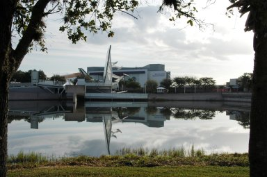 """KENNEDY SPACE CENTER, FLA. -- The Space Mirror Memorial, seen in profile, is reflected in the nearby lake at the KSC Visitor Complex. The memorial is the scene of a ceremony being held in remembrance of the astronauts lost in the Apollo 1 fire: Virgil """"Gus"""" Grissom, Edward H. White II and Roger B. Chaffee. The mirror was designated as a national memorial by Congress and President George Bush in 1991 to honor fallen astronauts. Their names are emblazoned on the monument's 42-1/2-foot-high by 50-foot-wide black granite surface as if to be projected into the heavens. Photo credit:NASA/George Shelton"""