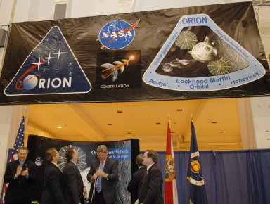 KENNEDY SPACE CENTER, FLA. -- After a ceremony to commemorate the transition of the historic Operations and Checkout (O&C) Building high bay for use by the Constellation Program, representatives from NASA, Lockheed Martin, Space Florida and the state of Florida look at the banner, unfurled by Kennedy Space Center Director Bill Parsons (center), spotlighting the Orion crew exploration vehicle that will be assembled in the O&C. From left are Russell Romanella, director of the International Space Station/Payload Processing Directorate at Kennedy Space Center; Thad Altman, representative of the State of Florida; Cleon Lacefield, Lockheed Martin program manager; Parsons; Steve Koller, executive director of Space Florida (turned away); and Skip Hatfield, Orion Project manager. Originally built to process space vehicles in the Apollo era, the O&C Building will serve as the final assembly facility for the Orion crew exploration vehicle. Orion, America's human spaceflight vehicle of the future, will be capable of transporting four crewmembers for lunar missions and later will support crew transfers for Mars missions. Each Orion spacecraft also may be used to support up to six crewmembers to the International Space Station after the space shuttle is retired in 2010. Design, development and construction of Orion's components will be performed by Lockheed Martin for NASA at facilities throughout the country. Photo credit: NASA/Kim Shiflett