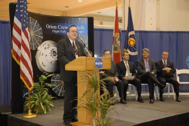 KENNEDY SPACE CENTER, FLA. -- Skip Hatfield, Orion Project manager, addresses guests and attendees in the Operations and Checkout (O&C) Building high bay in the ceremony commemorating the bay's transition for use by the Constellation Program. Seated on the dais at right are representatives from NASA, Lockheed Martin, Space Florida and the state of Florida: Russell Romanella, director of the International Space Station/Payload Processing Directorate at Kennedy Space Center, Cleon Lacefield, Lockheed Martin program manager; Thad Altman, representative of the State of Florida; Bill Parsons, director of Kennedy Space Center; and Steve Koller, executive director of Space Florida. Originally built to process space vehicles in the Apollo era, the O&C Building will serve as the final assembly facility for the Orion crew exploration vehicle. Orion, America's human spaceflight vehicle of the future, will be capable of transporting four crewmembers for lunar missions and later will support crew transfers for Mars missions. Each Orion spacecraft also may be used to support up to six crewmembers to the International Space Station after the space shuttle is retired in 2010. Design, development and construction of Orion's components will be performed by Lockheed Martin for NASA at facilities throughout the country. Photo credit: NASA/Kim Shiflett