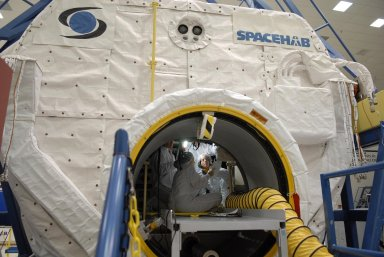 KENNEDY SPACE CENTER, FLA. -- Members of the STS-118 crew take part in a hardware review of the SPACEHAB module, part of the payload on their mission. Seen here is Mission Specialist Barbara Morgan, facing forward at the entrance of the module. The mission payload also includes the third starboard truss segment (ITS S5), a control moment gyro and the external stowage platform 3 (ESP3). STS-118 is targeted to launch June 28 from Launch Pad 39A. Photo credit: NASA/Kim Shiflett