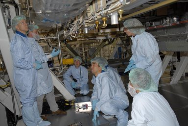KENNEDY SPACE CENTER, FLA. -- In the Space Station Processing Facility, astronauts Tim Kopra (left), Soichi Noguchi (center) and Sandra Magnuson (right, standing) get a close look at the Node 2 module. They and other astronauts are familiarizing themselves with the various elements to be installed on the International Space Station on future spaceflights. With construction of the Space Station the primary focus of future shuttle missions, astronaut crews will be working with one or more of the elements and hardware already being processed in the SSPF. Photo credit: NASA/Kim Shiflett