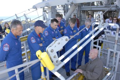 KENNEDY SPACE CENTER, FLA. -- At the 195-foot level of the fixed service structure on Launch Pad 39A, STS-117 crew members receive instruction on emergency egress during Terminal Countdown Demonstration Test activities. From left are Mission Specialist Danny Olivas, Commander Rick Sturckow, Pilot Lee Archambault, and Mission Specialists James Reilly, Steven Swanson and Patrick Forrester. They are practicing the emergency egress procedure using the slidewire basket system to get off the pad. The TCDT also includes M-113 armored personnel carrier training, and a simulated launch countdown. The mission payload aboard Space Shuttle Atlantis is the S3/S4 integrated truss structure, along with a third set of solar arrays and batteries. The crew of six astronauts will install the truss to continue assembly of the International Space Station. Photo credit: NASA/Kim Shiflett