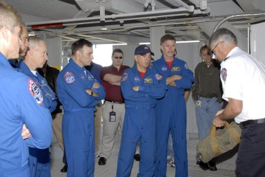 KENNEDY SPACE CENTER, FLA. -- During Terminal Countdown Demonstration Test activities, the Mission STS-117 crew members receive instruction on emergency egress during a walkdown of the 195-foot level of the fixed service structure at Launch Pad 39A. From the left are Mission Specialists Steven Swanson, Danny Olivas and Patrick Forrester, Pilot Lee Archambault, Commander Rick Sturckow and Mission Specialist James Reilly. The TCDT also includes M-113 armored personnel carrier training, and a simulated launch countdown. The mission payload aboard Space Shuttle Atlantis is the S3/S4 integrated truss structure, along with a third set of solar arrays and batteries. The crew of six astronauts will install the truss to continue assembly of the International Space Station. Photo credit: NASA/Kim Shiflett