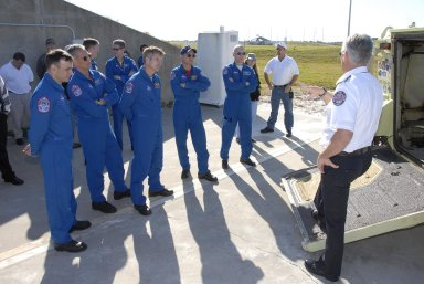 KENNEDY SPACE CENTER, FLA. -- Mission STS-117 crew members receive emergency egress instruction at Launch Pad 39A during Terminal Countdown Demonstration Test activities. From the left in front are Pilot Lee Archambault, Mission Specialists Danny Olivas and Steven Swanson, Commander Rick Sturckow and Mission Specialist Patrick Forrester. Directly behind Olivas is Mission Specialist James Reilly. At right is a partial view of the M-113 armored personnel carrier. The TCDT also includes M-113 armored personnel carrier training, and a simulated launch countdown. The mission payload aboard Space Shuttle Atlantis is the S3/S4 integrated truss structure, along with a third set of solar arrays and batteries. The crew of six astronauts will install the truss to continue assembly of the International Space Station. Photo credit: NASA/Kim Shiflett