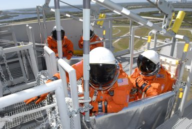 KENNEDY SPACE CENTER, FLA. -- From the 195-foot level of the fixed service structure on Launch Pad 39A, STS-117 Mission Specialists Patrick Forrester (front) and Steven Swanson sit in a slidewire basket, part of the emergency egress system. They and other crew members are practicing the emergency egress procedure to get off the pad, part of the prelaunch preparations known as terminal countdown demonstration test (TCDT). The TCDT also includes M-113 armored personnel carrier training and payload familiarization. The STS-117 mission is No. 21 to the International Space Station. Mission payloads aboard Atlantis include the S3/S4 integrated truss structure, a third set of solar arrays and batteries. The crew of six astronauts will install the truss to continue assembly of the station. Launch is scheduled for no earlier than March 15. Photo credit: NASA/Kim Shiflett.
