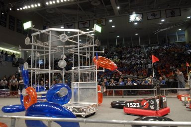 """KENNEDY SPACE CENTER, FLA. -- Competing robots try to loop the large meta target with colored rings. The robots are products of student teams taking part in the FIRST robotics event held at the University of Central Florida Arena March 8-10. The FIRST, or For Inspiration and Recognition of Science and Technology, Robotics Competition challenges teams of young people and their mentors to solve a common problem in a six-week timeframe using a standard """"kit of parts"""" and a common set of rules. Teams build robots from the parts and enter them in a series of competitions designed by FIRST founder Dean Kamen and Dr. Woodie Flowers, chairman and vice chairman of the Executive Advisory Board respectively, and a committee of engineers and other professionals. FIRST redefines winning for these students. Teams are rewarded for excellence in design, demonstrated team spirit, gracious professionalism and maturity, and ability to overcome obstacles. Scoring the most points is a secondary goal. Winning means building partnerships that last. Photo credit: NASA/Kim Shiflett"""