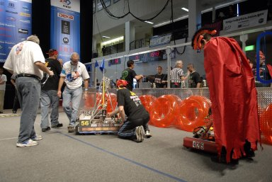 """KENNEDY SPACE CENTER, FLA. -- A Kissimmee, Fla., team (right) prepares its robot for competition with a New Jersey team (center) during the FIRST robotics event held at the University of Central Florida Arena March 8-10. The FIRST, or For Inspiration and Recognition of Science and Technology, Robotics Competition challenges teams of young people and their mentors to solve a common problem in a six-week timeframe using a standard """"kit of parts"""" and a common set of rules. Teams build robots from the parts and enter them in a series of competitions designed by FIRST founder Dean Kamen and Dr. Woodie Flowers, chairman and vice chairman of the Executive Advisory Board respectively, and a committee of engineers and other professionals. FIRST redefines winning for these students. Teams are rewarded for excellence in design, demonstrated team spirit, gracious professionalism and maturity, and ability to overcome obstacles. Scoring the most points is a secondary goal. Winning means building partnerships that last. Photo credit: NASA/Kim Shiflett"""