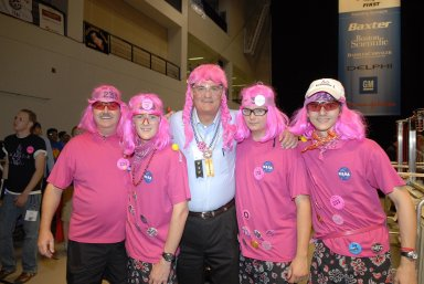 """KENNEDY SPACE CENTER, FLA. -- During the FIRST robotics event held at the University of Central Florida Arena March 8-10, Center Director Bill Parsons (center) dons the pink wig that represents team no. 233, composed of students from Rockledge, Cocoa Beach and Viera High Schools in Central Florida. The team is cosponsored by NASA KSC. The FIRST, or For Inspiration and Recognition of Science and Technology, Robotics Competition challenges teams of young people and their mentors to solve a common problem in a six-week timeframe using a standard """"kit of parts"""" and a common set of rules. Teams build robots from the parts and enter them in a series of competitions designed by FIRST founder Dean Kamen and Dr. Woodie Flowers, chairman and vice chairman of the Executive Advisory Board respectively, and a committee of engineers and other professionals. FIRST redefines winning for these students. Teams are rewarded for excellence in design, demonstrated team spirit, gracious professionalism and maturity, and ability to overcome obstacles. Scoring the most points is a secondary goal. Winning means building partnerships that last. Photo credit: NASA/Kim Shiflett"""