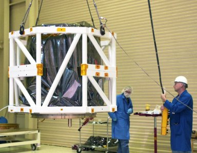 KENNEDY SPACE CENTER, FLA. -- In Building 1555 on North Vandenberg Air Force Base in California, technicians lift the AIM spacecraft via the spacecraft handling fixture attached to it. AIM, which stands for Aeronomy of Ice in the Mesosphere, is being prepared for integrated testing and a flight simulation. The AIM spacecraft will fly three instruments designed to study polar mesospheric clouds located at the edge of space, 50 miles above the Earth's surface in the coldest part of the planet's atmosphere. The mission's primary goal is to explain why these clouds form and what has caused them to become brighter and more numerous and appear at lower latitudes in recent years. AIM's results will provide the basis for the study of long-term variability in the mesospheric climate and its relationship to global climate change. AIM is scheduled to be mated to its launch vehicle, Orbital Sciences' Pegasus XL, during the second week of April, after which final inspections will be conducted. Launch is scheduled for April 25.
