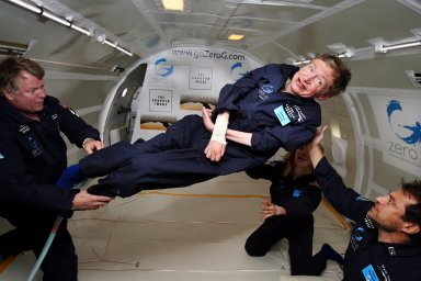 KENNEDY SPACE CENTER, FLA. -- Noted physicist Stephen Hawking (center) enjoys zero gravity during a flight aboard a modified Boeing 727 aircraft owned by Zero Gravity Corp. (Zero G). Hawking, who suffers from amyotrophic lateral sclerosis (also known as Lou Gehrig's disease) is being rotated in air by (right) Peter Diamandis, founder of the Zero G Corp., and (left) Byron Lichtenberg, former shuttle payload specialist and now president of Zero G. Kneeling below Hawking is Nicola O'Brien, a nurse practitioner who is Hawking's aide. At the celebration of his 65th birthday on January 8 this year, Hawking announced his plans for a zero-gravity flight to prepare for a sub-orbital space flight in 2009 on Virgin Galactic's space service. Photo credit: Jim Campbell, Aero-News Network