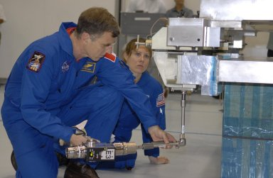 KENNEDY SPACE CENTER, FLA. --The STS-118 crew members look over parts of the mission payload, the S5 integrated truss, in the Space Station Processing Facility during crew equipment interface test activities. Seen here are Mission Specialists Dr. Dafydd Williams and Tracy Caldwell. The crew comprises Commander Scott Kelly, Pilot Charles Hobaugh, and Mission Specialists Williams, Barbara Morgan, Richard Mastracchio, Caldwell and Benjamin Drew. Williams is with the Canadian Space Agency. The STS-118 mission will be delivering the third starboard truss segment, the ITS S5, to the International Space Station, and a SPACEHAB Single Cargo module with supplies and equipment. Launch aboard Space Shuttle Endeavour is targeted for August. Photo credit: NASA/Kim Shiflett