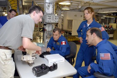 KENNEDY SPACE CENTER, FLA. -- In Orbiter Processing Facility bay 2, during crew equipment interface test activities, STS-118 Mission Specialists Dr. Dafydd Williams, Tracy Caldwell and Richard Mastrocchio get instructions on using photo equipment for their flight. The STS-118 mission will be delivering the third starboard truss segment, the ITS S5, to the International Space Station, as well as the SPACEHAB single cargo module filled with supplies and equipment. Launch aboard Space Shuttle Endeavour is targeted for Aug. 9. Photo credit: NASA/Kim Shiflett