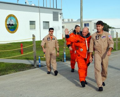 KENNEDY SPACE CENTER, Fla. -- Dressed in their launch and entry suits, STS-118 Pilot Charlie Hobaugh and Commander Scott Kelly (waving) are headed for the runway for landing practice in the shuttle training aircraft, known as an STA. The practice is part of Terminal Countdown Demonstration Test, or TCDT, activities that include a simulated launch countdown. The STA is a Grumman American Aviation-built Gulf Stream II jet that was modified to simulate an orbiter's cockpit, motion and visual cues, and handling qualities. In flight, the STA duplicates the orbiter's atmospheric descent trajectory from approximately 35,000 feet altitude to landing on a runway. The STS-118 mission is the 22nd flight to the International Space Station and is targeted for launch on Aug. 7. The mission payload aboard Space Shuttle Endeavour includes the S5 truss, a SPACEHAB module and external stowage platform 3. NASA/George Shelton