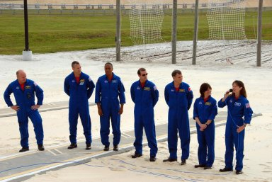 KENNEDY SPACE CENTER, Fla. -- On the slidewire basket bunker area of Launch Pad 39A, the STS-118 crew talks to the media before the crew's morning training activities in the terminal countdown demonstration test, or TCDT. At right, Mission Specialist Tracy Caldwell has the microphone. The others, from left, are Commander Scott Kelly, Pilot Charlie Hobaugh and Mission Specialists Alvin Drew, Rick Mastracchio, Dave Williams and Barbara Morgan. Williams represents the Canadian Space Agency. Morgan joined NASA's Teacher in Space program in 1985 and was selected as an astronaut in 1998. TCDT activities include M-113 training, payload familiarization, the emergency egress training at the pad and a simulated launch countdown. The mission is the 22nd flight to the International Space Station and Space Shuttle Endeavour will carry a payload including the S5 truss, a SPACEHAB module and external stowage platform 3. STS-118 is targeted for launch on Aug. 7. NASA/George Shelton
