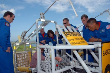 KENNEDY SPACE CENTER, Fla. -- On an upper level of the Pad 39A fixed service structure, the STS-118 crew members get directions about using the slidewire basket that is part of the emergency egress system. At left is Mission Specialist Rick Mastracchio. At right are (from the left) Commander Scott Kelly, Mission Specialist Barbara R. Morgan, Pilot Charlie Hobaugh and Mission Specialists Dave Williams and Alvin Drew. Morgan joined NASA's Teacher in Space program in 1985 and was selected as an astronaut in 1998. Williams represents the Canadian Space Agency. The crew is at Kennedy for training activities in the terminal countdown demonstration test, or TCDT. TCDT activities include M-113 training, payload familiarization, the emergency egress training at the pad and a simulated launch countdown. The mission is the 22nd flight to the International Space Station and Space Shuttle Endeavour will carry a payload including the S5 truss, a SPACEHAB module and external stowage platform 3. STS-118 is targeted for launch on Aug. 7. NASA/George Shelton