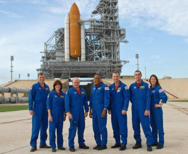 KENNEDY SPACE CENTER, Fla. -- The STS-118 crew poses for a photo on Launch Pad 39A during training activities in the terminal countdown demonstration test, or TCDT. From left are Mission Specialists Dave Williams and Barbara R. Morgan, Commander Scott Kelly, Mission Specialist Alvin Drew, Pilot Charlie Hobaugh, and Mission Specialists Rick Mastracchio and Tracy Caldwell. Williams represents the Canadian Space Agency. Morgan joined NASA's Teacher in Space program in 1985 and was selected as an astronaut in 1998. Behind them can be seen the solid rocket boosters and external tank of Space Shuttle Endeavour atop the mobile launcher platform. TCDT activities include M-113 training, payload familiarization, the emergency egress training at the pad and a simulated launch countdown. The mission is the 22nd flight to the International Space Station and Space Shuttle Endeavour will carry a payload including the S5 truss, a SPACEHAB module and external stowage platform 3. STS-118 is targeted for launch on Aug. 7. Photo credit: NASA/George Shelton