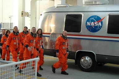 KENNEDY SPACE CENTER, Fla. -- The smiling STS-118 crew walks toward the Astrovan that will take them to Launch Pad 39A for a simulated launch countdown. From left are Mission Specialists Barbara R. Morgan and Rick Mastracchio, Pilot Charlie Hobaugh, Mission Specialists Dave Williams and Tracy Caldwell, and Commander Scott Kelly. Morgan joined NASA's Teacher in Space program in 1985 and was selected as an astronaut in 1998. The countdown concludes the terminal countdown demonstration test, or TCDT. The STS-118 crew has been at Kennedy for the TCDT activities that also include M-113 training, payload familiarization and emergency egress training at the pad. The mission is the 22nd flight to the International Space Station and Space Shuttle Endeavour will carry a payload including the S5 truss, a SPACEHAB module and external stowage platform 3. STS-118 is targeted for launch on Aug. 7. Photo credit: NASA/George Shelton